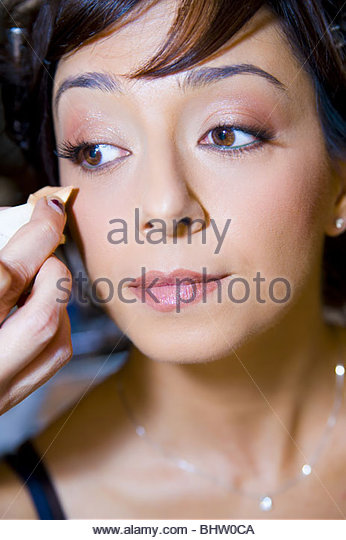 Make up artist clearing out smudge on woman face during a make up session - Stock Image