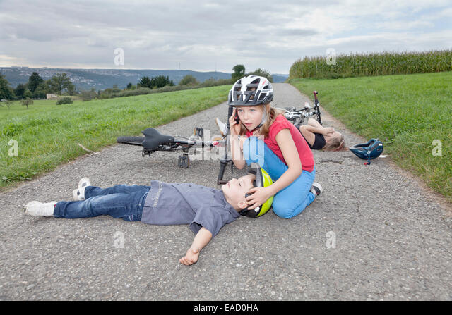 Girl, 9 years, phoning for help after a bicycle accident - Stock Image