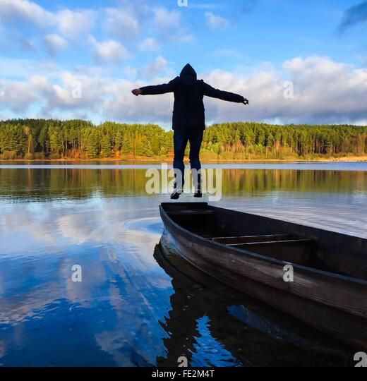 Man Jumping On Boat On Lake - Stock Image