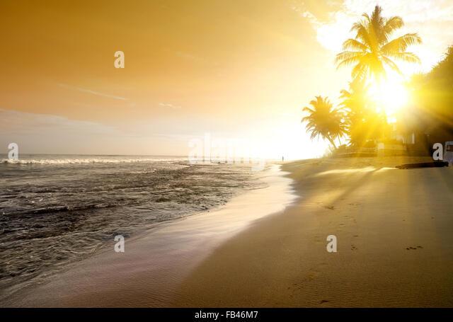 Orange sky over ocean and sandy beach - Stock Image