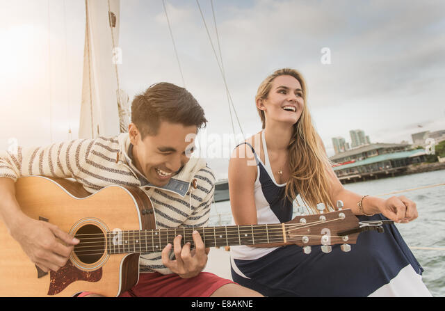 Young couple on sailing boat, man playing guitar - Stock Image