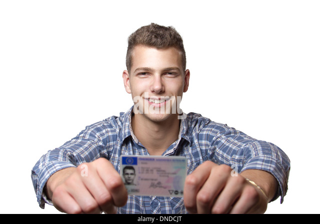 Young man just recieved his drivers license and is happy to drive his own car soon - Stock Image