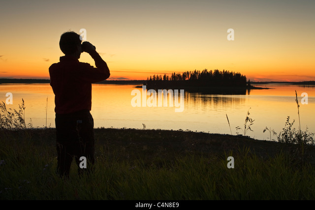 Middle age male hiker looking out over Astotin Lake with binoculars at dusk, Elk Island Park, Alberta, Canada. - Stock Image