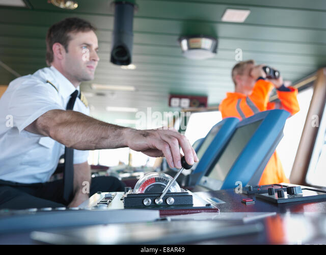 Captain and ship worker on ship's bridge - Stock Image