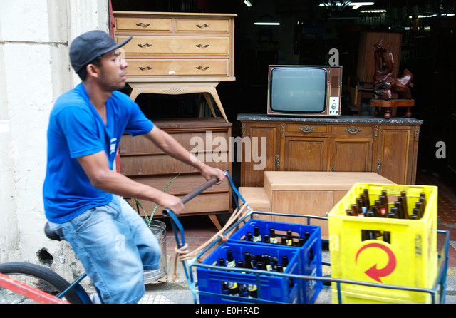 SAO PAULO, BRAZIL - SEPTEMBER 28, 2013: Brazilian man rides a bicycle along the city street delivering bottles of - Stock Image