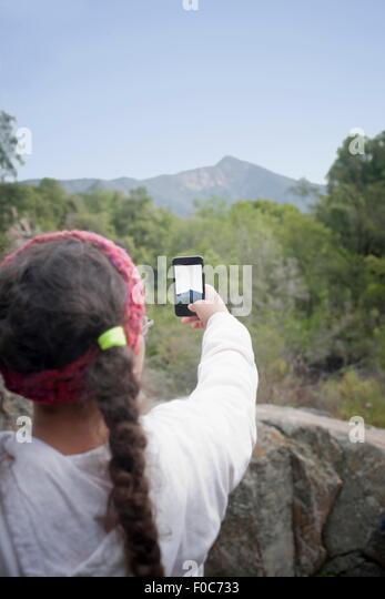 Young girl taking photo of view with smartphone, Valparaiso. Chile - Stock Image