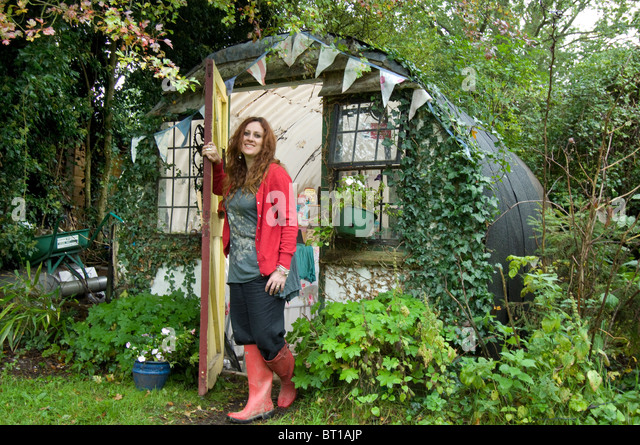 woman in red wellington boots at the door of her office and garden shed made from an old corrugated iron bomb shelter - Stock Image