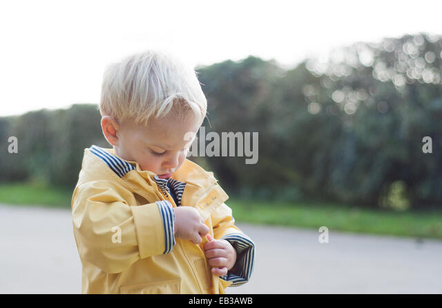Boy zipping up rain coat - Stock Image