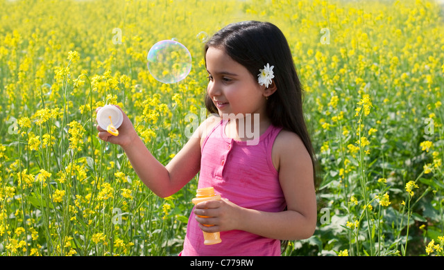Young girl making bubbles in a field - Stock Image