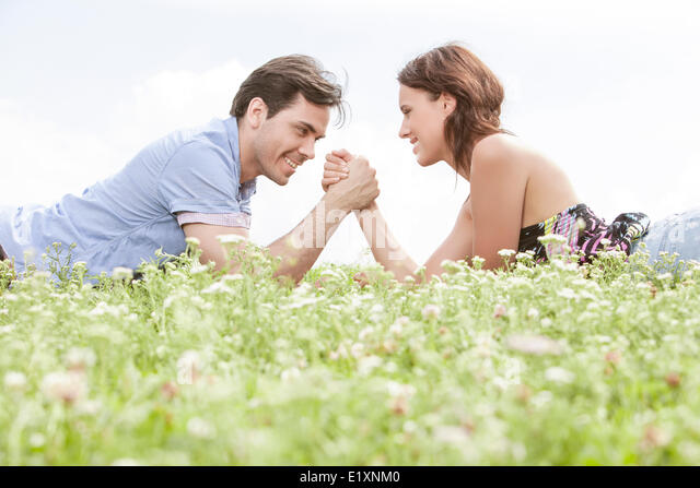 Side view of young couple arm wrestling while lying on grass against sky - Stock Image