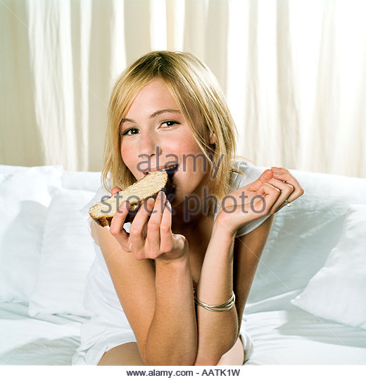 young woman eating a slice of bread and butter - Stock Image
