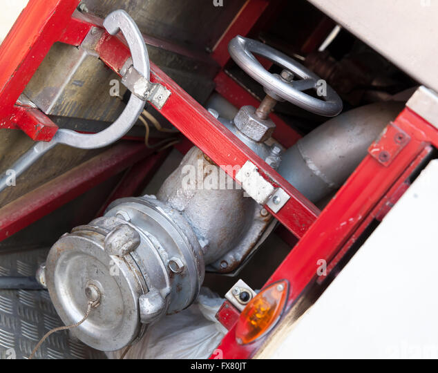 Firefighting equipment on red fire truck. Water hydrant closeup photo with selective focus - Stock Image