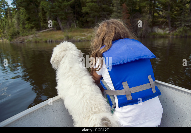 Little girl with little white dog in boat; Lake of the Woods, Lulu, Ontario, Canada - Stock Image