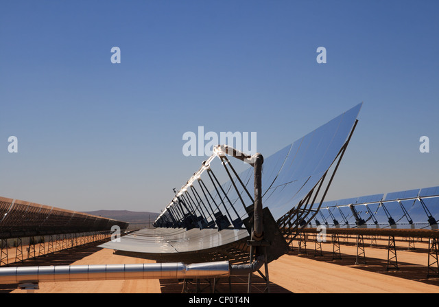 SEGS solar thermal energy desert electricity plant with parabolic mirrors concentrating the sunlight with blue sky - Stock Image