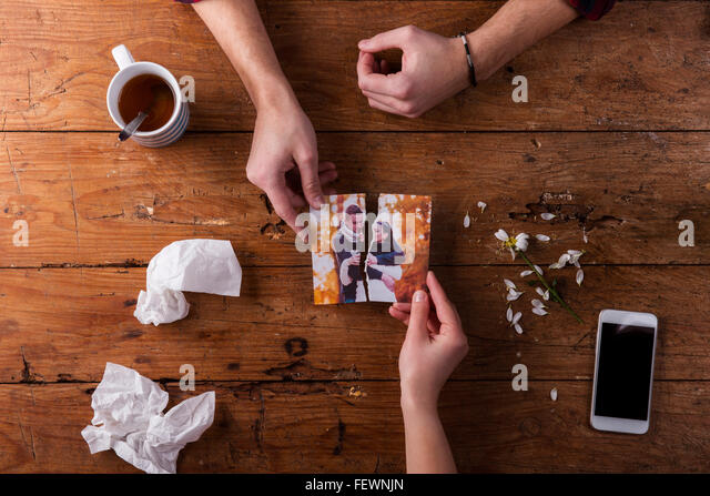 Sad mans, womans hands holding torn picture of romantic couple. - Stock-Bilder