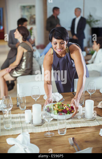 Woman serving food at dinner party - Stock Image