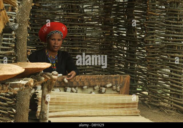View of Zulu wife in traditional dress weaving sleeping mat Shakaland theme village KwaZulu-Natal South Africa Cultures - Stock-Bilder
