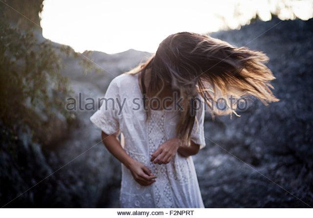 Mixed race woman twirling hair in remote field - Stock-Bilder