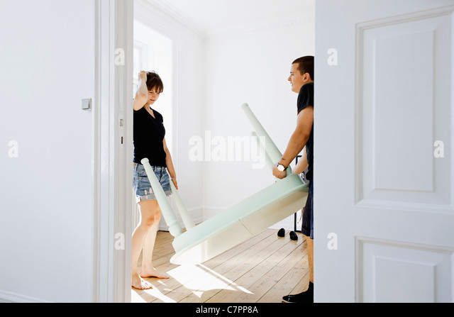 Couple carrying table in new home - Stock Image