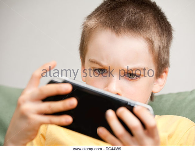 Boy playing game console - Stock Image