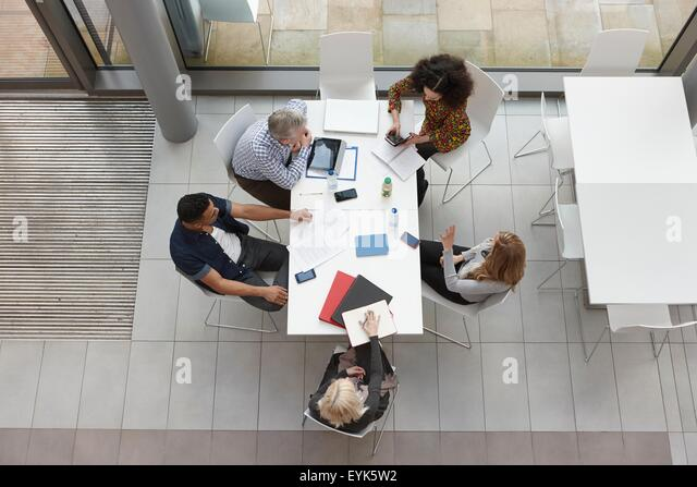 Overhead view of business team having meeting at conference table - Stock Image