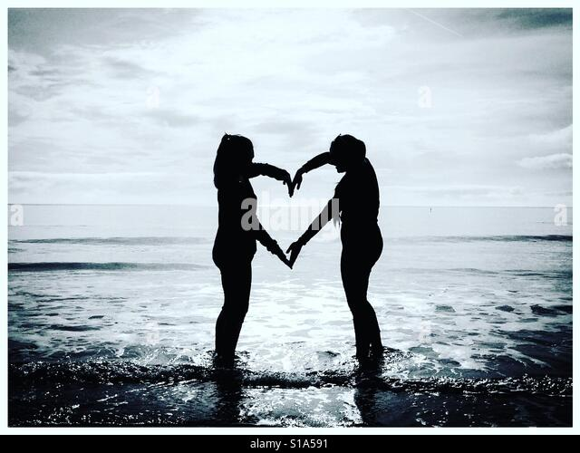 Two people on a beach making a heart sign with the sea in the background - Stock-Bilder