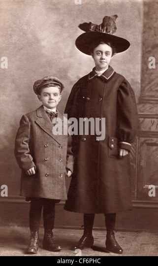 A vintage photo of a boy and girl dressed up in overcoats and hats,  circa 1908. - Stock Image