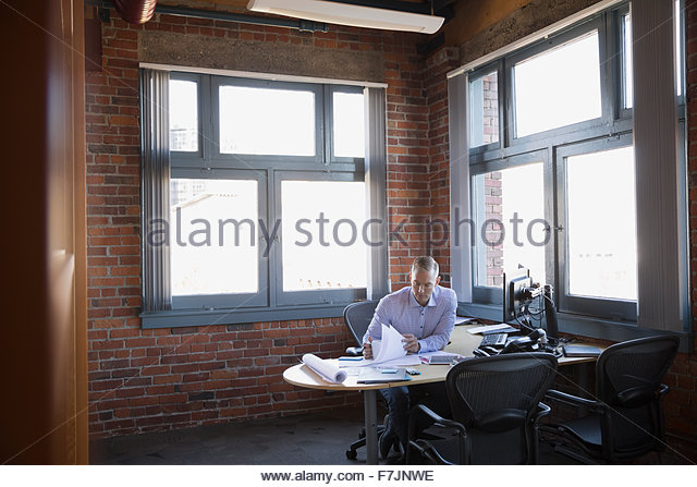 Businessman reviewing paperwork at office desk - Stock Image