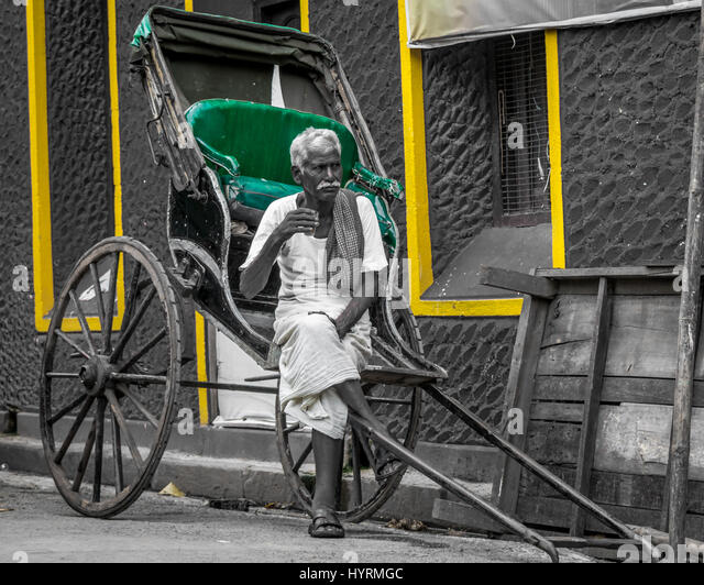 A hand rickshaw puller taking a tea beak and being thoughtful - Stock Image