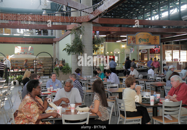 Nashville Tennessee Nashville Farmers' Market food court dining tables groups dining lunch Black man woman business - Stock Image