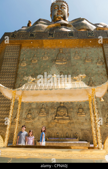 Young tourists standing beneath large statue of buddha - Stock Image