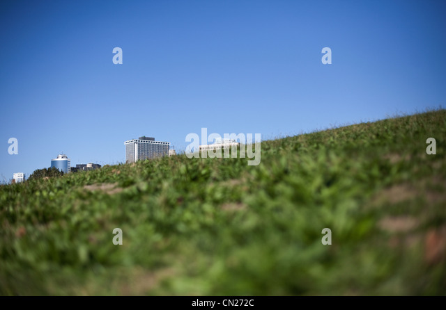 Buildings behind grassy hill - Stock-Bilder