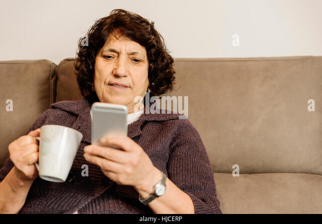 Senior woman using his mobile phone at home. - Stock Image