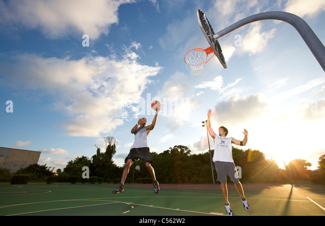 male scoring during outdoor basketball scrimmage between two young men - Stock Image