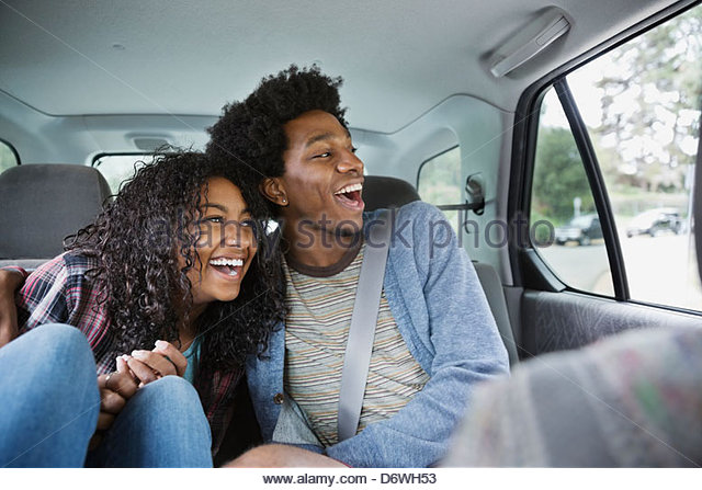 Cheerful couple looking through window while enjoying road trip - Stock Image