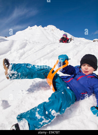 small  happy boy sledging fast down a steep snow covered hill with little girl and blue sky behind - Stock Image