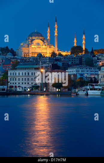Lights of Suleymaniye Mosque Istanbul reflected at dawn on Golden Horn water Turkey - Stock Image