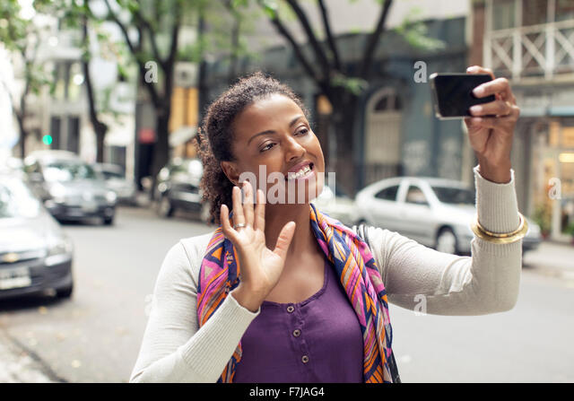 Woman doing video chat on street - Stock Image