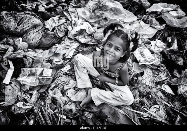 Poor Indian lower caste girl sitting in a rubbish tip. Andhra Pradesh, India. Monochrome - Stock Image