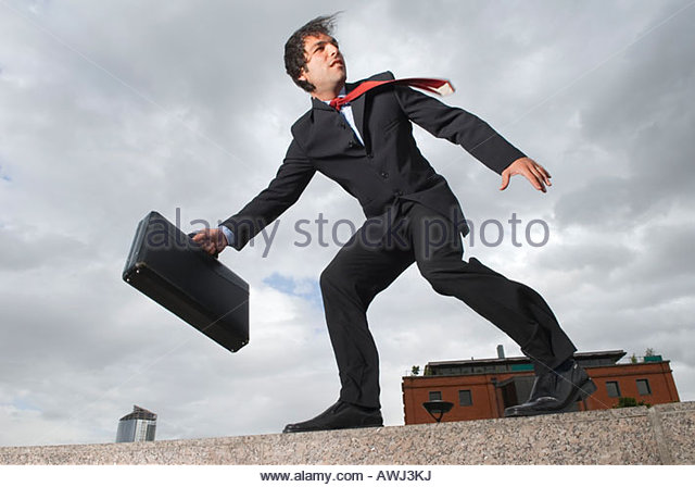 Businessman with briefcase standing on windy ledge - Stock Image
