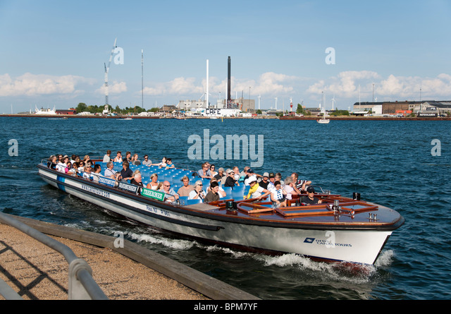 A canal cruise boat preparing to dock at one of the many stops on a tour in Copenhagen, Denmark. - Stock Image