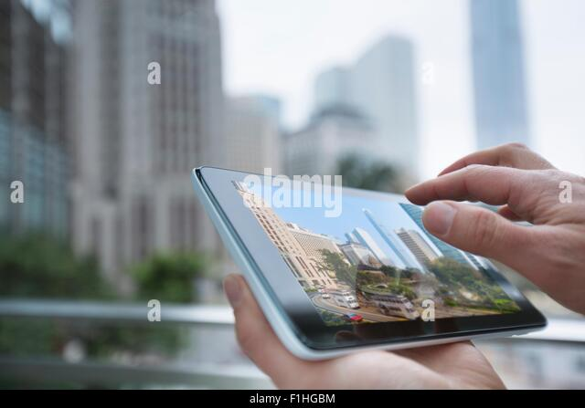 Man using digital tablet, focus on hands, Hong Kong, China - Stock Image