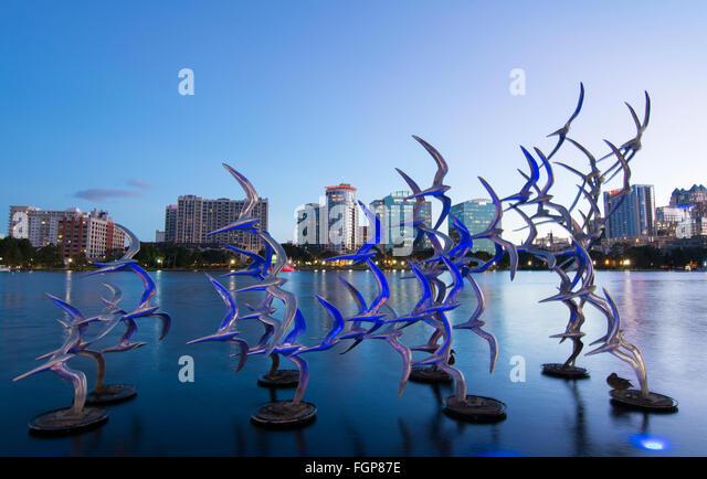 Orlando Florida Lake Eola Take Flight Douse Blumberg skyline twilight colored lights on statue birds with skyline - Stock Image