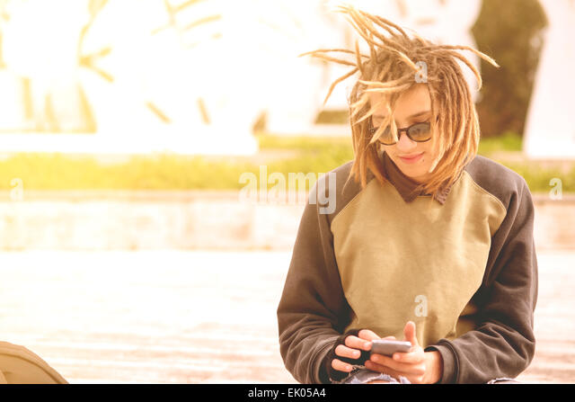 Lifestyle portrait of a young man using a smart phone outdoors warm tones filter applied - Stock-Bilder