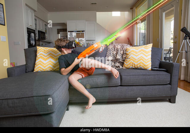 Young boy on sofa, wearing virtual reality headset, firing laser guns, digital composite - Stock-Bilder