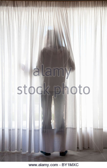 Silhouette of figure through curtains - Stock-Bilder