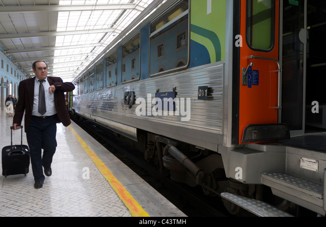 Passenger with suitcase next to an intercity train in Santa Apolónia railway station in Lisbon, Portugal, Europe - Stock-Bilder