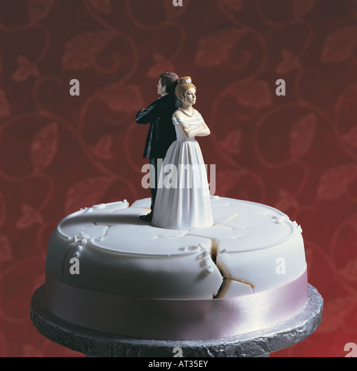 A wedding cake, bride and groom standing back to back - Stock Image