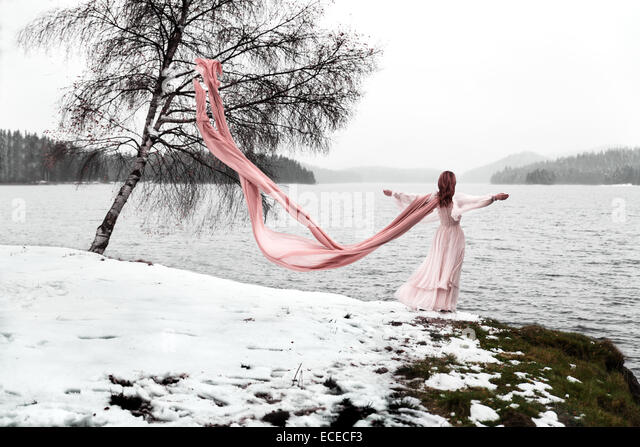 woman with long scarf standing by a lake in winter - Stock Image