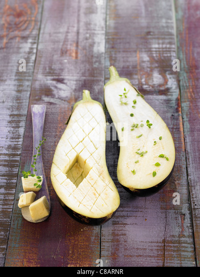 Half a checkered eggplant and half an eggplant with herbs - Stock Image